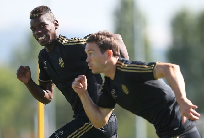 Juventus' French midfielder Paul Pogba (L) and Swiss defender Stephan Lichtsteiner take part in a training session on the eve of an UEFA Champions League football match against Manchester City on September 14, 2015 at the 'Juventus Training Center' in Vinovo, near Turin.  AFP PHOTO / MARCO BERTORELLO        (Photo credit should read MARCO BERTORELLO/AFP/Getty Images)