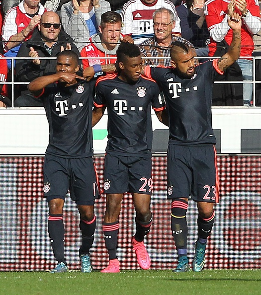 Bayern Munich's French forward Kingsley Coman (L) celebrates scoring the 3-0 with Bayern Munich's Brazilian midfielder Douglas Costa (L) and Bayern Munich's Chilean midfielder Arturo Vidal during the German first division Bundesliga football match 1 FSV Mainz 05 vs FC Bayern Muenchen in Mainz, central Germany, on September 26, 2015. AFP PHOTO / DANIEL ROLAND RESTRICTIONS: DURING MATCH TIME: DFL RULES TO LIMIT THE ONLINE USAGE TO 15 PICTURES PER MATCH AND FORBID IMAGE SEQUENCES TO SIMULATE VIDEO.  == RESTRICTED TO EDITORIAL USE == FOR FURTHER QUERIES PLEASE CONTACT DFL DIRECTLY AT + 49 69 650050.        (Photo credit should read DANIEL ROLAND/AFP/Getty Images)
